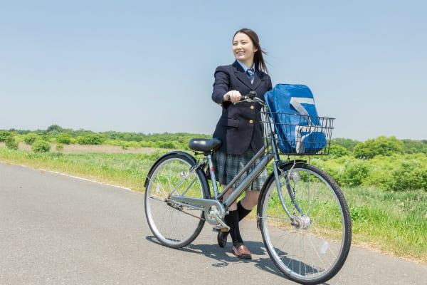 河原を自転車で通る女子高生