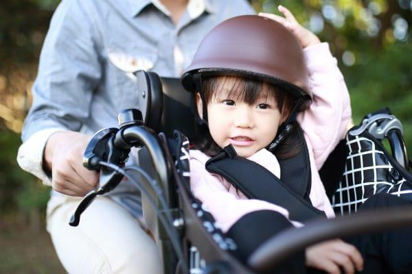 ヘルメットを被って自転車に乗る女の子